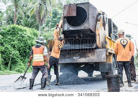 Small asphalt roller in on duty repairing repairing asphalt road. Workers on a road construction, industry and teamwork. stock photo