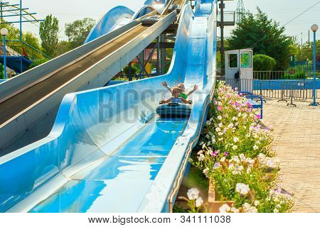 Children on a water slide, two boys descend on an inflatable boat in an amusement park. stock photo