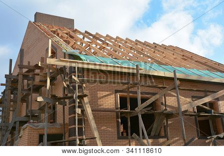 Unfinished brick house rooftop roofing construction attic trusses, wooden beams, eaves, timber, scaffolding.  House roof wooden frame roofing construction. stock photo
