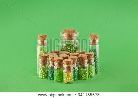 Green and yellow beads in glass jars on bright green background. Beads in a transparent container with a wooden cork. stock photo