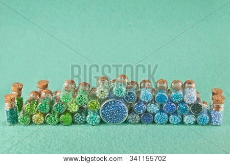 Blue, green, yellow and purple beads in glass jars on a bright cyan background. Beads in a transparent container with a wooden cork. The concept of orderliness, balance and chaos. stock photo