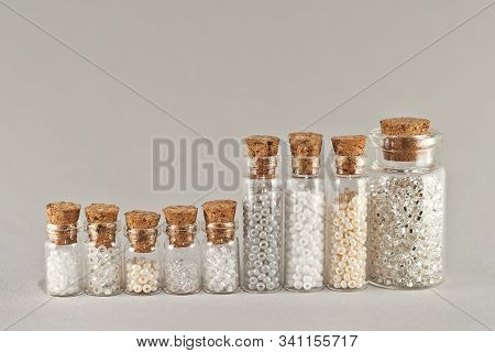 White, beige and yellow beads in glass jars on a gray background. Beads in a transparent container with a wooden cork. stock photo
