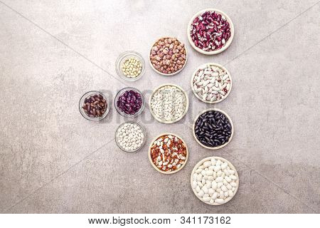 Assortment of beans on a stone background. Crimson cranberry, red, painted pony, black turtle, brown, black-eyed, Jacob's Cattle (heirloom), lima, navy, asparagus bean and soybean. stock photo