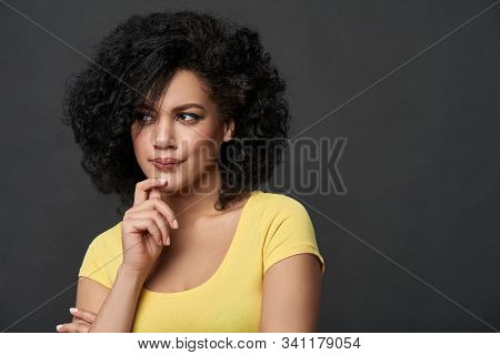 Doubtful frowning woman looking to side contemplating stock photo