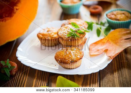 baked sweet pumpkin muffins with dried apricots inside, stock photo