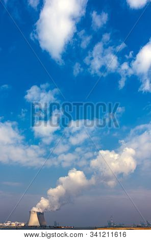 Power plant cooling towers emit white steam clouds in the blue sky stock photo