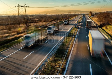 High intensity highway traffic with Delivery Lorry trucks passing in both directions. Intense Highway transportation with delivery trucks stock photo