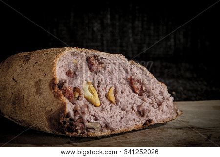 Wine flavoured bread (pain au vin) with its typical red inside, stuffed with walnuts, on display on a wooden plank. it is a typical old French snack. stock photo