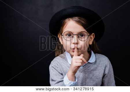 Adorable little girl in smart casualwear and eyeglasses asking you to keep quiet against black background in isolation stock photo