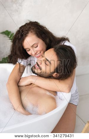 Happy young affectionate woman embracing her relaxed husband enjoying bath with hot water and foam stock photo