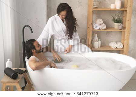Happy young woman in white bathrobe sitting on bathtub and talking to her husband enjoying bath with foam stock photo