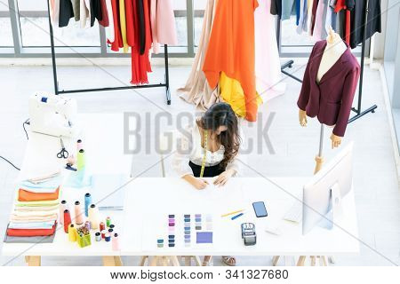 Top view of young adult fashion designer drawing and sketching her work at her atelier studio with colour palette as sole owner. Using for entrepreneur startup concept. stock photo