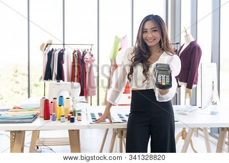 Portrait of young adult fashion designer hold EDC Machine ready for customer to make a payment with credit card at her atelier studio as sole owner. Using for entrepreneur startup and consumerism  stock photo