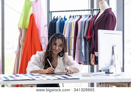 Young adult fashion designer drawing and sketching her work eith digital tablet at her atelier studio with colour palette as sole owner. Using for entrepreneur startup concept. stock photo