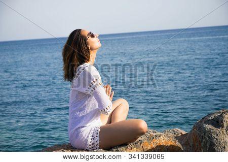 Girl doing yoga on tropical beach. Yoga on the beach. Yoga lifestyle. Healthy lifestyle. Girl doing yoga on the beach. Concept of healthy lifestyle. Happy people. Healthy people. Young people. Anjali mudra namaste. stock photo