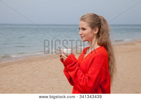 Beautiful blonde woman drinks hot drink on sea beach stock photo