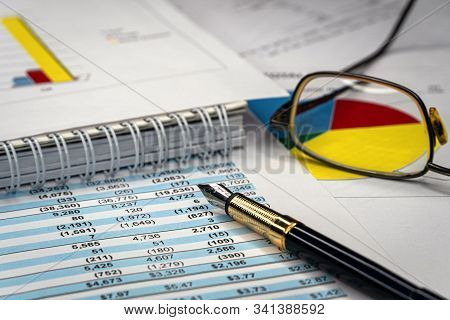 Accounting business. Glasses and pen with accounting report stock photo