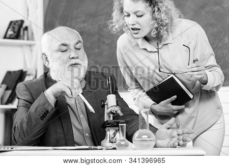 Biologist or chemist with microscope teaching student biology. Study biology. Biological research. College university education. Teacher and girl with notepad near chalkboard. Biology science stock photo
