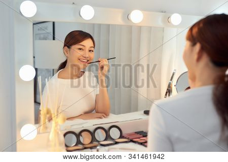 Beautiful Woman With Beauty Face Applying Lip Balm, Lipcare Stick On. Lips skincare cosmetics concept. stock photo