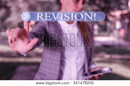Handwriting text writing Revision. Concept meaning action of revising over someone like auditing or accounting Business woman in the nature pointing with the finger into empty space. stock photo