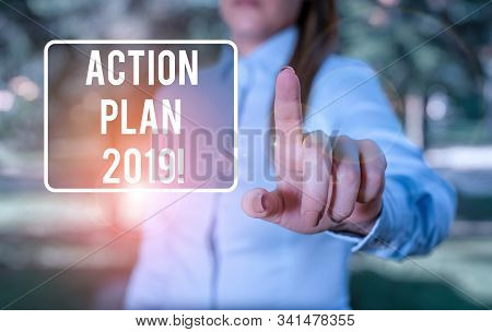 Handwriting text writing Action Plan 2019. Concept meaning proposed strategy or course of actions for current year Woman in a blue business shirts pointing with her finger into empty space. stock photo