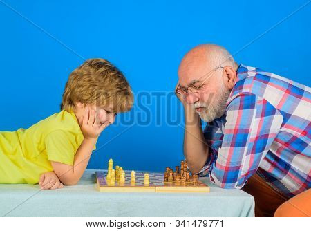 Games and activities for children. Checkmate. Little boy think or plan chess game. Grandfather and grandson playing chess. Child boy playing chess with grandfather. Little boy learning to play chess. stock photo