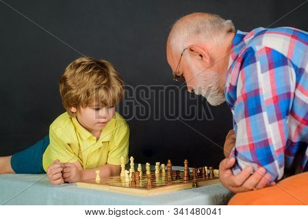 Child boy playing chess with grandfather. Games and activities for children. Checkmate. Little boy think or plan chess game. Grandfather and grandson playing chess. Little boy learning to play chess. stock photo