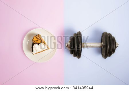 Eating sweet carb food opposed to doing sports and athletics. A heavy lifting dumbbell next to a plate with rich on carbonhydrates cake stock photo