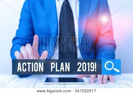 Writing note showing Action Plan 2019. Business photo showcasing proposed strategy or course of actions for current year Businessman with pointing finger in front of him. stock photo