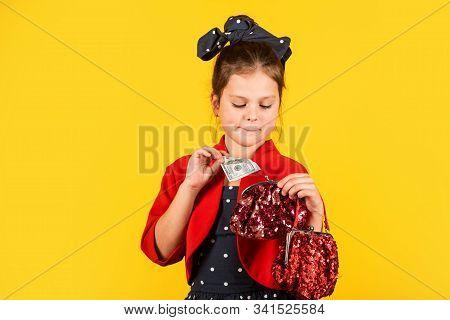 Born to be rich. Little girl put dollars in money bag. Small child save cash money. Money savings. Deposit money into savings account stock photo
