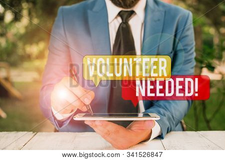 Text sign showing Volunteer Needed. Conceptual photo asking demonstrating to work for organization without being paid Businessman pointing with pen in empty copy space. stock photo