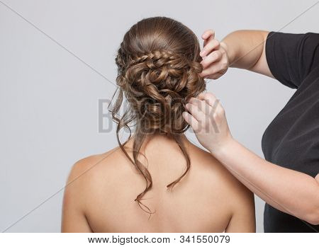 Portrait of a beautiful sensual light brown haired woman with a wedding hairstyle in a beauty salon. The hairdresser does the hairstyle. Wedding hairstyle. stock photo