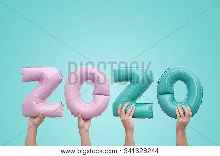 Hands holding numbers numbers 2020 made of pink and mint foil balloons on neo mint background. Greeting card to celebrate 2020 Happy New Year with copy space stock photo