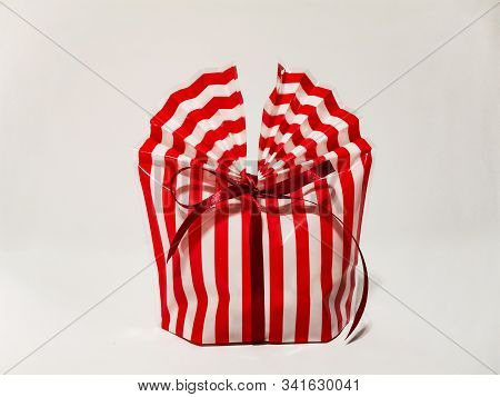 Beautiful striped packing bag tied with a red ribbon with a bow. Gift wrap. Nice gift, surprise. stock photo