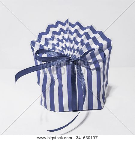 Beautiful striped packing bag tied with a blue ribbon with a bow. Gift wrap. Nice gift, surprise. stock photo