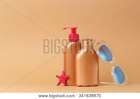 Sunblock ads, sun protection cosmetic products design with moisturizer cream or liquid lotion on bronze, light brown background. Facial and body skin care on the beach, at sea, on summer vacation. stock photo