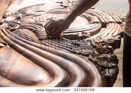 beautiful carved woodwork in an Indian street workshop. The hands of an Indian carpenter polishing the carved wooden headboard. stock photo