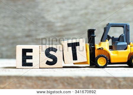 Toy forklift hold letter block t to complete word est (abbreviation of established, estimated, eastern time zone, expressed sequence tag) on wood background stock photo