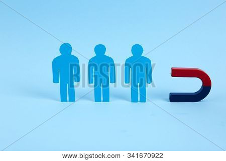 Magnet attracting paper people on light blue background stock photo