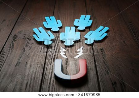 Magnet attracting paper people on wooden background stock photo