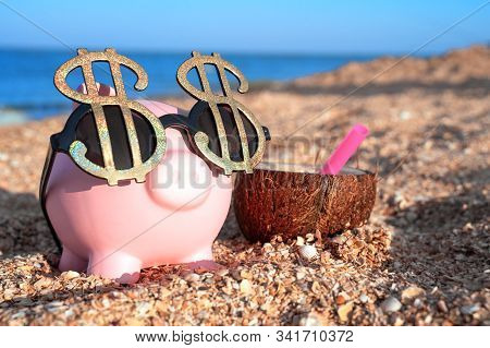 Pink piggy bank with sunglasses of dollar sings, standing on the beach sand close to coconut cocktail. Saving money for travel concept. Copy space. stock photo