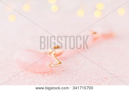real rose quartz facial roller closeup on pastel pink background with bokeh, soft focus stock photo