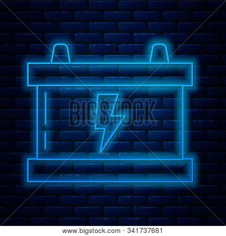 Glowing neon line Car battery icon isolated on brick wall background. Accumulator battery energy power and electricity accumulator battery. Lightning bolt. Vector Illustration stock photo