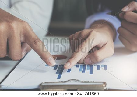 Close up of woman or accountant hand holding pen working on laptop computer for calculate business data, accountancy document and calculator at office, business concept stock photo
