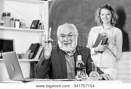 Study biology. College university education. Biologist or chemist with microscope teaching student biology. Biology science. Biological research. Teacher and girl with notepad near chalkboard stock photo