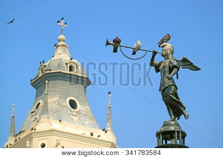 Historic Statue of Angel of the Fame on the Fountain at Plaza Mayor in Lima with Relaxing Doves and Blurry Cathedral Belfry in Background, Peru stock photo