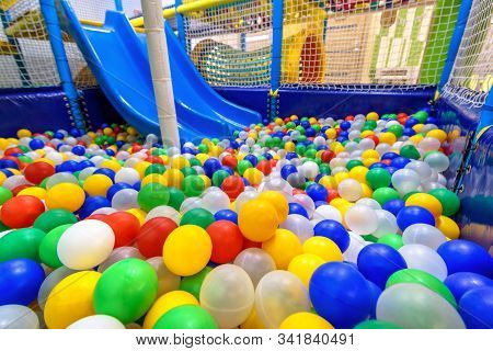 Kids playground indoor. Panoramic view inside the dry pool with colorful balls and slide. Nice plastic gym for activity in playroom. Closeup of colored balls in children playground for sport and play. stock photo