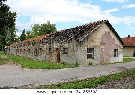 Abandoned red brick military barrack with destroyed roof and missing roof tiles on cracked dilapidated facade with broken windows surrounded with paved road and uncut grass at abandoned military complex stock photo