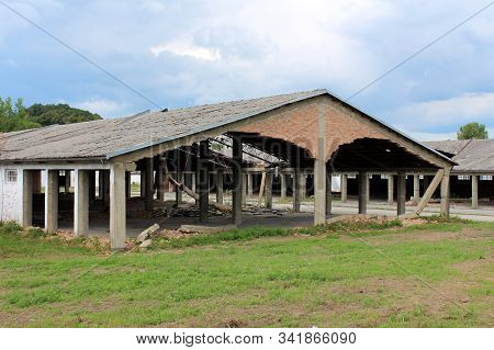 Densely built wide large hangar buildings with missing destroyed red brick support walls and unusual bent roofs surrounded with paved area mixed with grass and trees at abandoned military complex on cloudy blue sky background stock photo