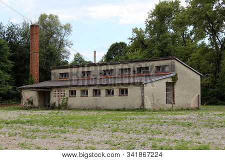 Dilapidated old military barrack with broken windows and missing doors next to tall red brick chimney surrounded with grass and dense trees at abandoned military complex stock photo